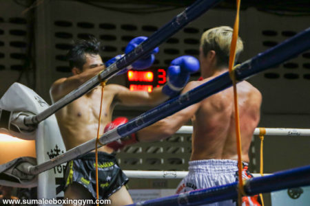 Max fending off opponent at Patong Boxing Stadium